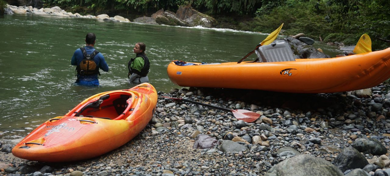 Duckie and a kayak in the shore of the river.